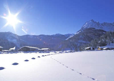 Kirchdorf_KAM_000188_Spuren-im-Schnee-vor-Haeusern-und-Bergen_Fotograf-Albin-Niederstrasser
